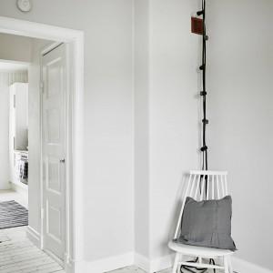 Na tle podłogi z bielonego drewna oraz szarych i białych ścian, czarne okablowanie pełni funkcję dekoracyjną, dodającą mieszkaniu mocniejszego wyrazu. Fot. Stadshem/Jonas Bergman.