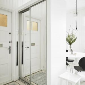 Przestrzeń kuchni i jadalni zamknięto zabudową, pełniącą rolę zarówno ścianki działowej, jak i garderoby. Praktyczny element zamykają drzwi, pokryte lustrzaną taflą, które optycznie powiększają wnętrze. Fot. Stadshem/Jonas Bergman.