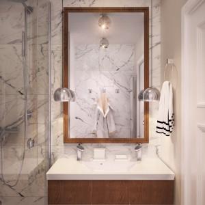 Ściany i podłogi w łazience i toalecie zaplanowano w marmurowym wykończeniu. Szlachetny materiał nadaje przestrzeni luksusowy charakter. Projekt: Studio projektowe Geometrium.