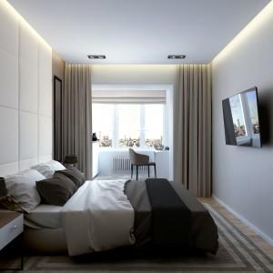 Za łóżkiem w sypialni zaplanowano miękki, tapicerowany zagłówek, poprowadzony pod sam sufit. Pod sam sufit zdają się również prowadzić drzwi wejściowe do pomieszczenia, przedłużone wizualnie o drewniany panel nad nimi w tym samym kolorze co ich skrzydło. Projekt: Studio projektowe Geometrium.