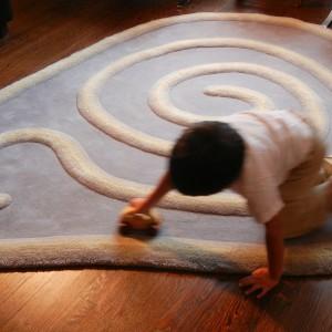 Dywan o nieregularnym kształcie i wzorze inspirowanym muszką ślimaka jest nie tylko praktyczną dekoracją. Może też służyć małym chłopcom jako tor wyścigowy do zabawy. Fot. Zoom.