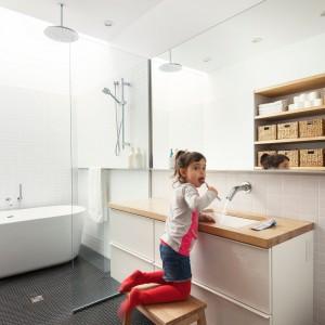 Wpadające do wnętrza naturalne światło, białe powierzchnie i duża, lustrzana tafla powiększają optycznie wnętrze. Drewniane elementy ocieplają wizualnie przestrzeń. Projekt: la SHED Architecture. Fot. Maxime Brouilette.