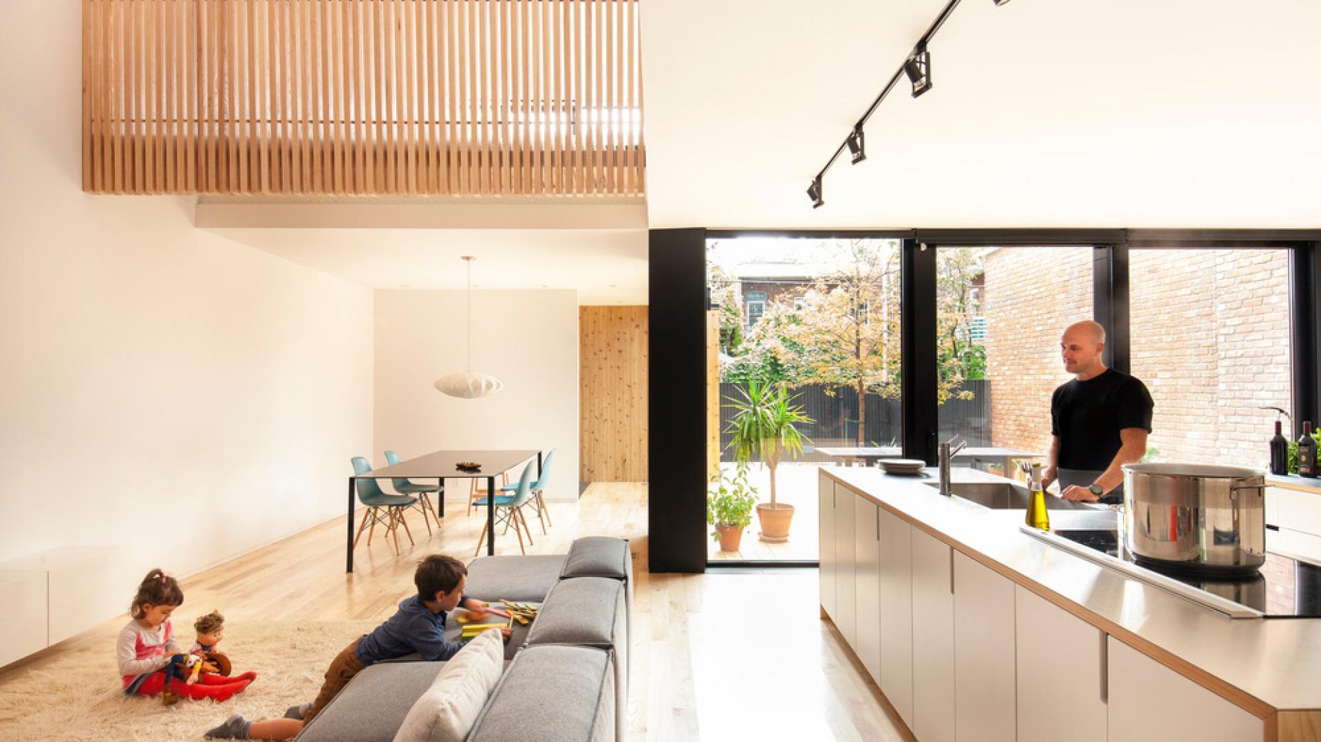 Dużą kuchnię otwarto na salon. Przestrzenne wnętrze wydaje się dodatkowo większe dzięki jasnym kolorom na ścianach i dużym przeszkleniom, wyglądającym na patio. Projekt: la SHED Architecture. Fot. Maxime Brouilette.
