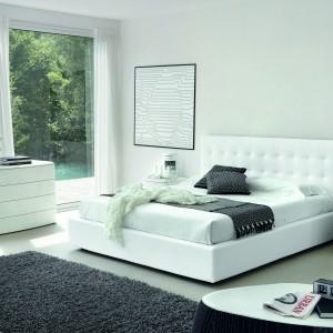 Nowoczesne łóżko z tapicerowanym wezgłowiem, komoda i szafka nocna z lakierowanymi frontami kreują nowoczesny styl białej sypialni. Pazura dodają aranżacji czarne dodatki, np. dywan czy lampka nocna. Fot. Go Modern Furniture.