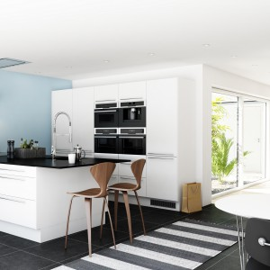 Biały, obszerny półwysep zwieńczono czarnym blatem, wysuniętym o kilka centymetrów, tak aby zapewnić wygodne miejsce na domowy bar. Mebel skomponowano z białą zabudową, w której czarnym akcentem jest wbudowany sprzęt AGD. Fot. Nettoline, kuchnia Paris.
