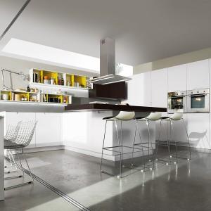 Białe meble przełamuje czarny blat wyspy. Ożywaj je z kolei kolor żółty zastosowany do wykończenie otwartych szafek górnych. Fot. Milton, kuchnia Nevi Cover.