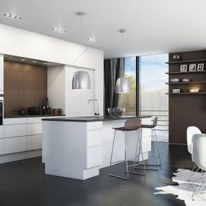 Kuchnia, na którą składa się wysoka zabudowa wpasowana we wnękę w ścianie i wyspa kuchenna, prezentuje się przepięknie w bieli, zwieńczonej ciemnym blatem. Fot. Svane.