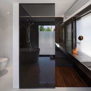W minimalistycznej łazience przestrzeń ociepla drewno na fragmencie podłogi oraz niewielki płomień ognia, wydobywający się z małego kotlarza. Projekt: Atelier Moderno. Fot. Stéphane Groleau.