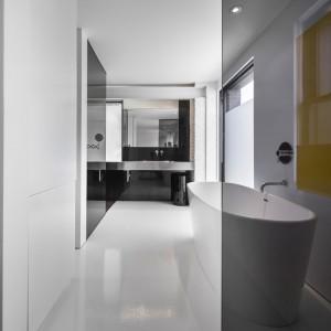 Dużą wolno stojącą wannę wpasowano w przestrzeń osłoniętą czarnym szkłem. Przeszklenie efektownie kontrastuje z jasną, jednorodną posadzką. Projekt: Atelier Moderno. Fot. Stéphane Groleau.
