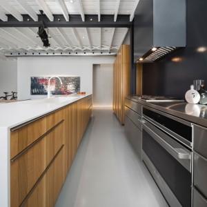 Nowoczesną kuchnię ocieplają fronty z drewnianym dekorem. Na tle chłodnych barw i hojnie użytej stali, stanowią przytulniejszy akcent aranżacyjny. Projekt: Atelier Moderno. Fot. Stéphane Groleau.