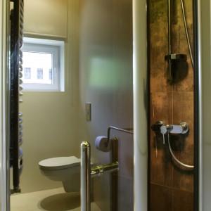 Armaturę prysznicową  zamontowano na wprost wejścia. To naścienna bateria oraz zestaw prysznicowy z drążkiem: wysokość, na której umieszczony jest uchwyt z rączka prysznicową można regulować. Dzięki temu  wygodnie korzystają z natrysku domownicy o różnym wzroście. Projekt: Ola Wołczyk. Fot. Bartosz Jarosz.