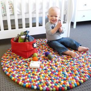 Po szóstym miesiącu życia, gdy maluch zaczyna siadać i szykuje się do raczkowania, warto kupić do pokoju kolorowy dywan. Zabezpieczy on malucha przed zimnem bijącym od podłogi, jak również pobudzi do zabawy. Fot. Happy as Larry Design.