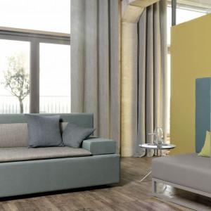 Wysokie okna i sufity oraz betonowa ściana to typowe cechy wnętrz w stylu loft. Żeby uczynić z nich nieszablonową przestrzeń można wykorzystać tkaniny - poduszki i zasłony dodadzą takiemu wnętrzu szyku i przytulności. Fot. Dekoma.
