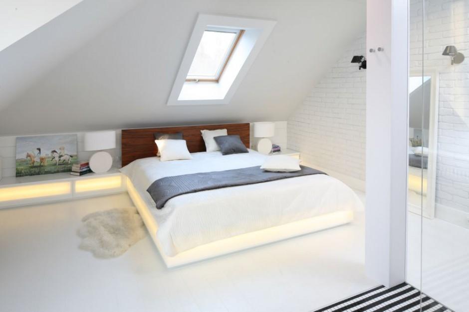 Sypialnię urządzono na poddaszu. Białe ściany i podłoga tworzą spójną przestrzeń. Dzięki zastosowaniu jasnych powierzchni wnętrze staje się przestronniejsze. Fot. Bartosz Jarosz.