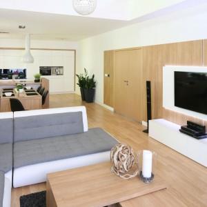 Białe panel telewizyjny zamontowany na udekorowanej drewnem ścianie stanowi główny element dekoracyjny salonu. do niego dobrano długą, niską szafkę rtv. Całkowicie zamknięta zawiera pojemne szafki. Projekt: Małgorzata Błaszczyk. Fot. Bartosz Jarosz.