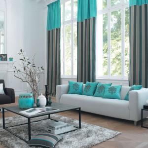Dekoracje okienne z serii Napoli marki Casadeco łączą w sobie dwa bardzo modne ostatnio kolory: szarość i turkus. Kolekcję uzupełniają poduszki dekoracyjne. Fot. Casadeco.