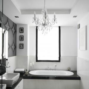 Kontrastem dla dominującej bieli jest kolor czarny: występuje tutaj pod postacią granitowego blatu oraz tapety z wytwornym wzorem na ścianie wokół lustra. Projekt: Magdalena Smyk. Fot. Bartosz Jarosz.