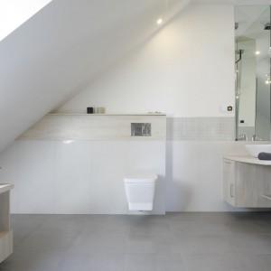 Urządzona w bieli łazienka na poddaszu jest nowoczesna i przestronna. Biel została delikatnie ocieplona za pomocą dekoru drewna w jasnym wybarwieniu. Projekt: Kamila Paszkiewicz. Fot. Bartosz Jarosz