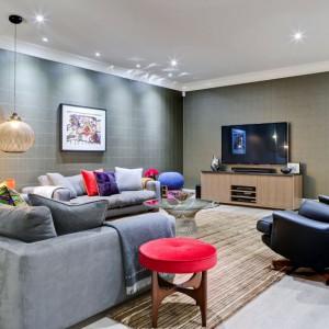 W mieszkaniu dwóch braci salon pełni funkcję pokoju imprez. Szare ściany i efektowne oświetlenie wpisują się w taki charakter przestrzeni. Projekt: Daniel Hopwood Studio. Fot. Matt Chung Photo.