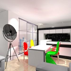 W kuchni zaplanowano pojemną biało-czarną zabudowę z dużą wyspą z akrylu z blatami z konglomeratu kwarcowego. Kolorowe krzesła świetnie kontrastują ze stonowanym wnętrzem. Projekt: Wioleta Bednarczyk, pracownia Glamloft. Fot. Wioleta Bednarczyk.