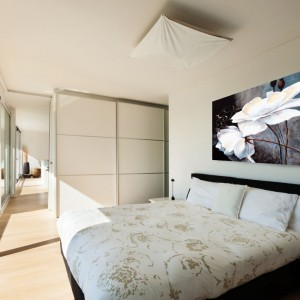 Jasna sypialnia sprzyja relaksowi. W takim wnętrzu ścianę nad łóżkiem pięknie ozdobią nadrukowane na płótnie kwiaty. Grafika dostępna na stronie Demural. Fot. Demural.