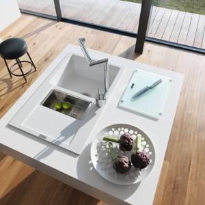 Biały zlewozmywak pięknie harmonizuje z białą wyspą kuchenną, ale idealny będzie też w zabudowie małej kuchni. Jasny kolor idealnie nadaje się do małego metrażu i pozwala dopasować zlewozmywak do mebli, a minimalistyczna forma nie przytłoczy aranżacji kuchni. Fot. Franke, zlewozmywak Maris 651-78.