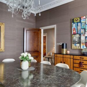 Jedno z pomieszczeń przeznaczono na niezależną jadalnię. Piękny stół, dekoracyjny żyrandol, sztukaterie pod sufitem i obraz w zdobnej ramie na ścianie przenoszą nas w rzeczywistość angielskich lordów. Projekt: Daniel Hopwood Studio. Fot. Matt Chung Photo.