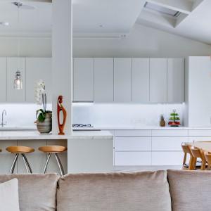 Kuchnię tworzy długa zabudowa na jedną ścianę oraz pokaźnych rozmiarów półwysep. Pod oknem wygospodarowano miejsce na duży stół jadalniany. Projekt: Daniel Hopwood Studio. Fot. Matt Chung Photo.