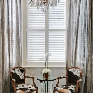 Piękne stylizowane meble budują we wnętrzu klimat wszechogarniającego luksusu. Tutaj efektowne krzesła z tekstylnym oparciem i siedziskiem w motyw zwierzęcy, zestawiono z eleganckim stolikiem o szklanej podstawie. Projekt: Daniel Hopwood Studio. Fot. Matt Chung Photo.