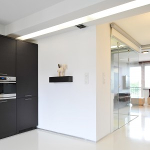 Przeszkloną łazienkę widać również z poziomu kuchni. Projekt: RS+ Architekci. Fot. Tomasz Zakrzewski.