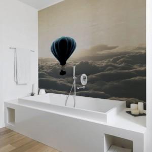 Fototapeta umieszczona na ścianie nad wanną dobrze komponuje się z bielą ścian i drewnianą podłogą. Fot. Dekornik.