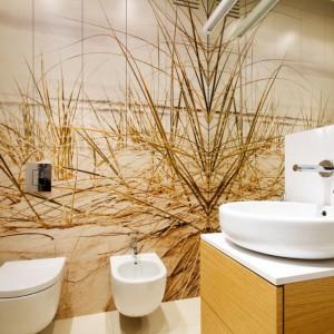 Spokojna łazienka utrzymana w ciepłej kolorystyce została optycznie powiększona dzięki wysokiej tafli lustra. Delikatny motyw morskich wydm został zwielokrotniony w lustrze tworząc ciekawy efekt wizualny. Projekt: Monika i Adam Bronikowscy. Fot. Monika i Adam Bronikowscy.