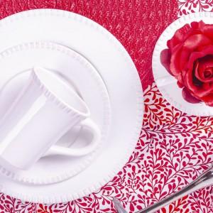 Biała porcelana zawsze sprawdzi się na wyjątkowe okazje. W połączeniu z czerwonym obrusem i innymi soczystymi dodatkami stworzy prawdziwie romantyczną atmosferę. Fot. Home&You.