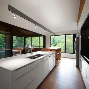 W kuchni dominują minimalistyczne formy. Gładkie fronty, proste linie i biel wpisują się w obowiązujące trendy. Projekt: Blouin Tardif Architecture-Environment. Fot. Steve Montpetit.