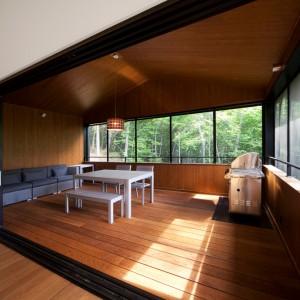 Poszczególne funkcje na piętrze zaplanowano w rzędzie, prowadzącym do zabudowanej werandy w drewnie. Domownicy mogą się tutaj zrelaksować w otoczeniu naturalnych materiałów, podziwiając krajobraz za oknem. Projekt: Blouin Tardif Architecture-Environment. Fot. Steve Montpetit.