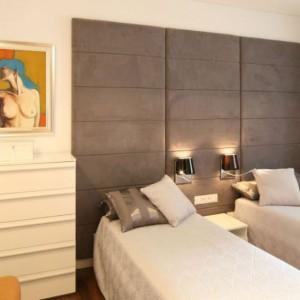 Sypialnia została urządzona w stonowanych barwach. Ciemna tapicerka z prostokątnymi podziałam kontrastuje z jasnymi ścianami i meblami. Projekt: Małgorzata Galewska. Fot. Bartosz Jarosz.