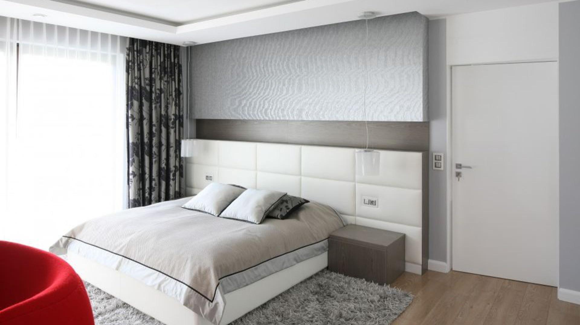 Ścianę za łóżkiem podzielono na trzy części. Dolną część obłożono białą tapicerką, która razem z łóżkiem w tym samym kolorze tworzy spójną całość. Ściana ta pełni również funkcję praktycznego zagłówka. Projekt: Agnieszka Hajdas-Obajtek. Fot. Bartosz Jarosz.