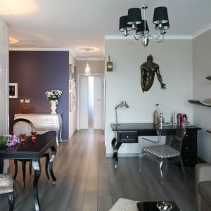 Gustowny stół i dwa eleganckie krzesła ustawiono przy ścianie, naprzeciw sofy narożnej. Osobne oświetlenie w postaci eleganckiego kinkietu podkreśla odrębność jadalni. Projekt: Joanna Nawrocka. Fot. Bartosz Jarosz.