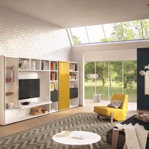 Salon o podwyższonej wysokości urządzono w modnej bieli. Na tle ceglanej ściany usytuowana duża meblościanka podkreśla nowoczesny charakter aranżacji. Fot. Hulsta.
