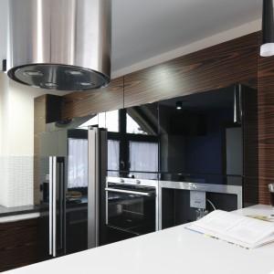 Wysoka zabudowa kuchenna została wykonana z dwóch warstw. Większa, stanowiąca tło, zyskała drewniany dekor, a mniejsza -czarna, w którą zabudowano sprzęty AGD, wykończona została na wysoki połysk. Projekt: Marta Kilan. Fot. Bartosz Jarosz.