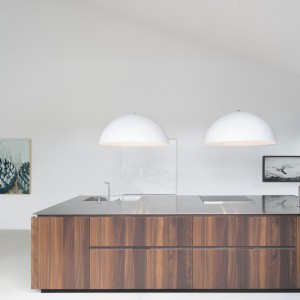 Centrum kuchni stanowi bardzo duża wyspa, wykonana z dębowego drewna i zwieńczona obszernym, stalowym blatem. Projekt: Thomas Balaban Architecture. Fot. Adrien Williams.
