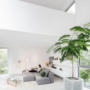 Salon z wysokim sufitem zyskuje dodatkowe wrażenie przestronności dzięki jasnym barwom, które zdominowały jego przestrzeń. Projekt: Thomas Balaban Architecture. Fot. Adrien Williams.