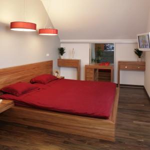Proste w formie drewniane łóżko i szafki doskonale pasują do czerwonych dodatków. Taki duet warto mieć w swojej sypialni. Projekt: Magdalena Olchowiak. Fot. Bartosz Jarosz.
