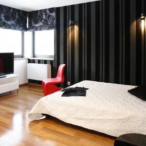 Czarno-białe wnętrze jest eleganckie i nowoczesne. Drewniana podłoga ociepla przestrzeń, a krzesło w czerwonym kolorze stanowi ciekawy kontrast. Projekt: Dąbrówka Potomska. Fot. Bartosz Jarosz.