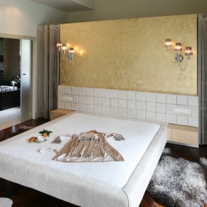 To sypialnia nowoczesna, ale i elegancka. Prostym formom szyku nadaje ściana wykończona tapetą w kolorze złota i dekoracyjne oświetlenie. Ciemna, drewniana podłoga ociepla przestrzeń. Projekt: Dominik Respondek. Fot. Bartosz Jarosz.