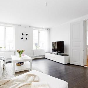 Szafkę RTV, stolik kawowa oraz meble wypoczynkowe utrzymano w bieli. Ciemna podłoga eksponuje je nad wyraz pięknie. Fot. Vastanhem.