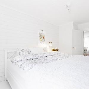 W sypialni stoi duże, dwuosobowe łóżko z pięknym ozdobnym zagłówkiem. Fot. Vastanhem.