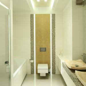 Symetryczny podział łazienki wyznacza podwieszany sufit, który został efektownie oświetlony. Poza delikatnym oświetleniem LED na suficie umieszczono lampę, która dostarcza sporo światła do wnętrza. Projekt: Karolina Łuczyńska. Fot. Bartosz Jarosz.