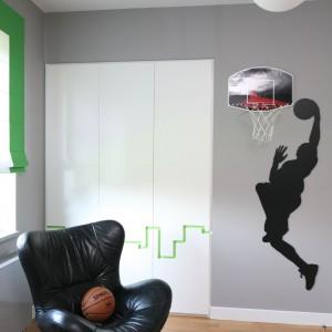 Aranżacja pokazuje, że w tym pokoju mieszka młody zawodnik koszykówki. Zdradza to ściana, na której zamontowano kosz do ulubionej gry gospodarza pokoju. Dekorację uzupełnia naklejka, prezentująca sylwetkę operującego piłką gracza. Projekt: Katarzyna Koszałka. Fot. Bartosz Jarosz.