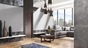 Jak urządzić salon w stylu loft? Najprościej będzie sięgnąć po modne szarości. Ściany czy podłogi w tym neutralnym kolorze pozwolą poczuć wielkomiejski klimat w każdym wnętrzu.